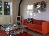 De woonkamer of sejour, met twee banken, een luie stoel en een houtkachel.