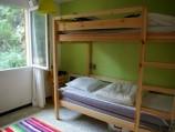 De groene kamer heeft een stapelbed en een lekker speelkleed voor kinderen.